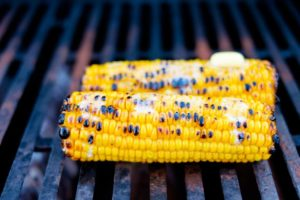 Corn topped with butter on the grill