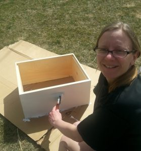 Chaya painting the bee boxes