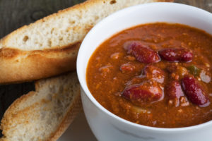 A bowl of chili con carne with toasted baguette